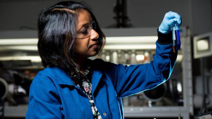Une femme noire, manipulant un tube à essai dans un laboratoire