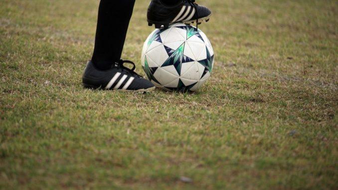Une joueuse de football avec le pied posé sur le ballon.