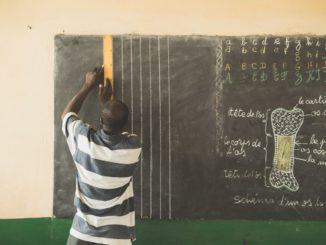 Un insrituteur au tableau dans une école de Kpevego, au Togo (Photo : Unsplash).