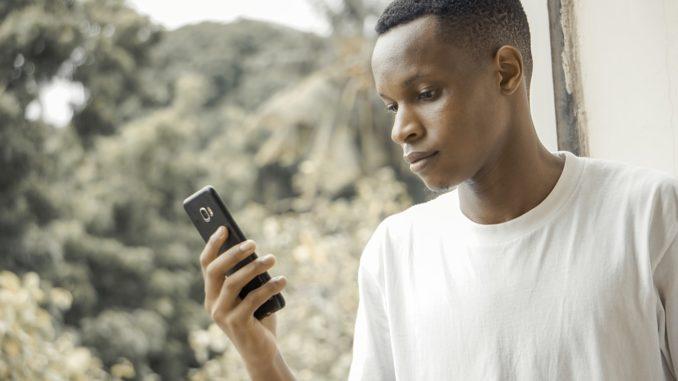 Un jeune africain tenant un smartphone en main.